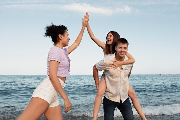 Gens heureux de coup moyen au bord de la mer