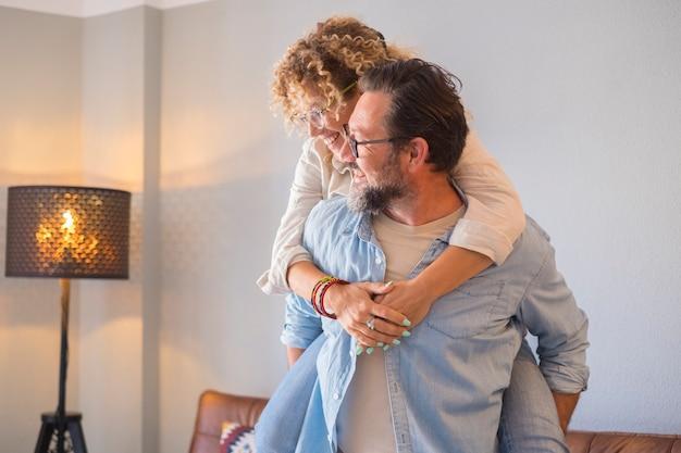 Des gens heureux couple homme et femme en ferroutage s'amuser et profiter ensemble de la maison en souriant