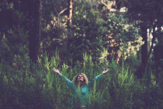 Gens heureux femme heureuse au milieu de la forêt de bois avec des arbres et des plantes partout autour - sauvez et respectez la nature aucune activité commerciale de déforestation - jour de célébration de l'événement de la terre