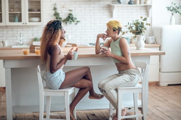 Gens heureux. femme à la peau sombre en short et petite amie caucasienne avec une coiffure courte pieds nus parler tranquillement souriant boire du café