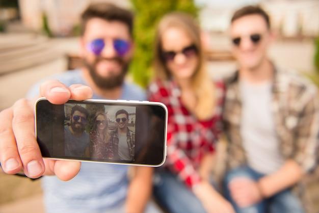Les gens heureux font selfie à l'extérieur.