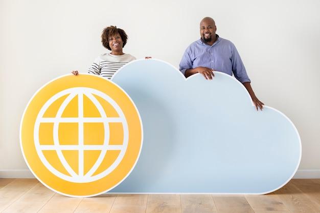 Les gens heureux avec des icônes de nuages et de la technologie