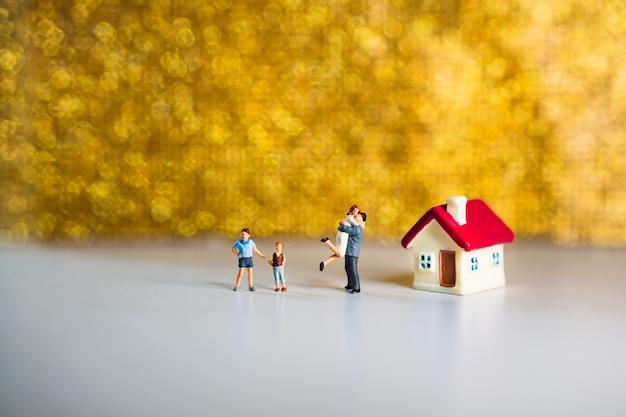 Gens heureux miniatures debout près de la maison