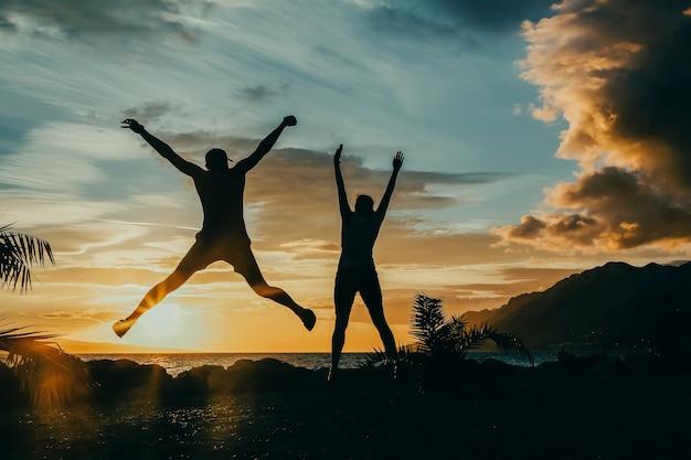 Gens heureux sautant par-dessus le coucher du soleil