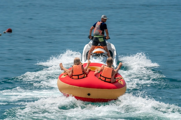 Des gens heureux vont nager sur un matelas pneumatique derrière un jet ski, les touristes montent sur le gonflable