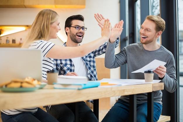Des gens intelligents agréables et positifs assis à la table et se sentant heureux tout en se donnant cinq