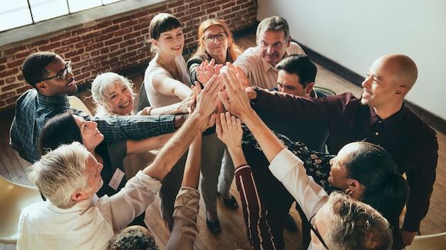 Les gens joignent les mains en l'air lors d'une réunion