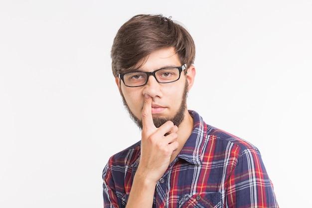 Les gens, le jour du poisson d'avril et le concept de geste - jeune homme cueillant son nez sur une surface blanche