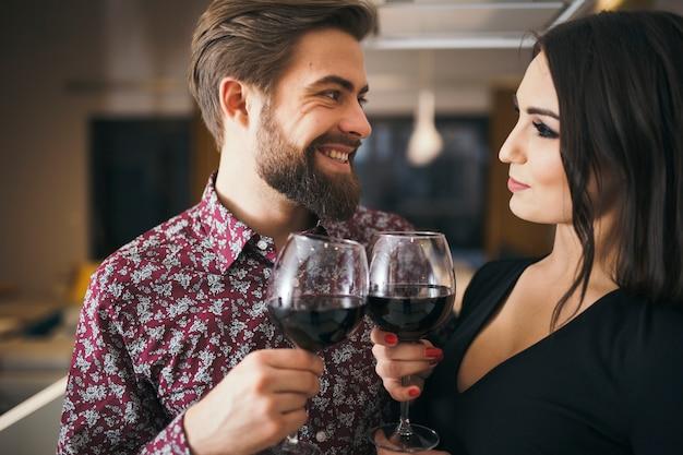 Gens joyeux appréciant la soirée romantique avec du vin