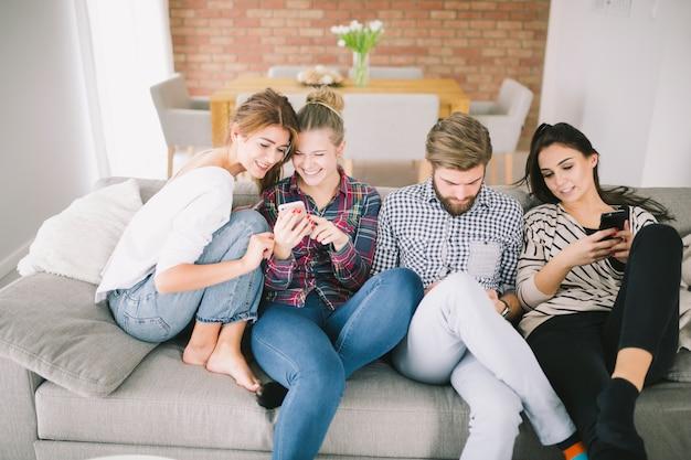 Gens joyeux avec des gadgets sur le canapé