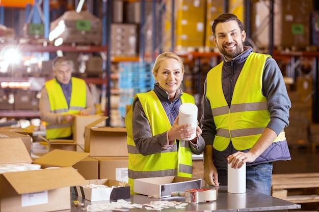 Des gens joyeux et positifs qui vous regardent tout en travaillant dans le secteur de la vente au détail en gros