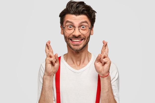 Les gens, le langage corporel et les attentes. heureux jeune homme de race blanche avec chaume, garde les doigts croisés, porte une chemise blanche avec des accolades rouges, a une expression heureuse, isolée sur le mur