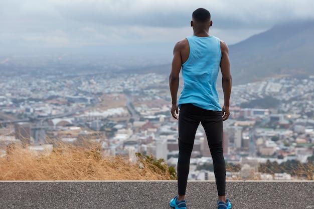 Gens, liberté, concept de mode de vie. vue arrière de l'homme sportif en vêtements de sport, se dresse haut sur la route, regarde d'en haut sur une vue magnifique sur la ville avec des gratte-ciel, ciel bleu et volcan, trains sport à l'extérieur