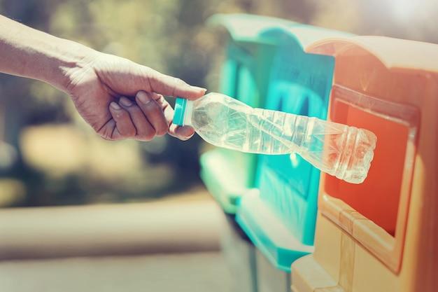 Gens, main, tenue, bouteille déchets plastique, mettre, dans, corbeille, pour, nettoyage