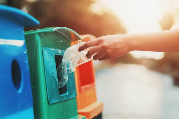 Gens, main, tenue, bouteille poubelle, plastique, mettre, dans, corbeille, pour, nettoyage