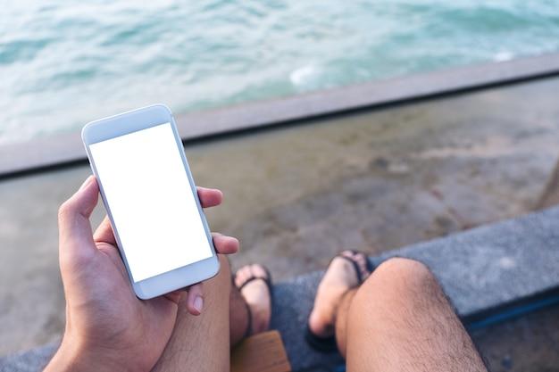 Les gens à la main en utilisant un téléphone intelligent maquette de la mer