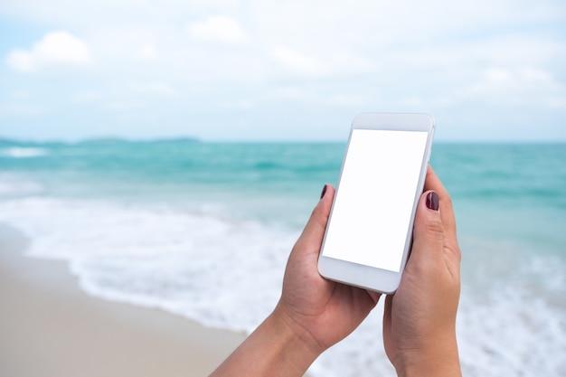 Les gens à la main en utilisant un téléphone intelligent maquette par mer