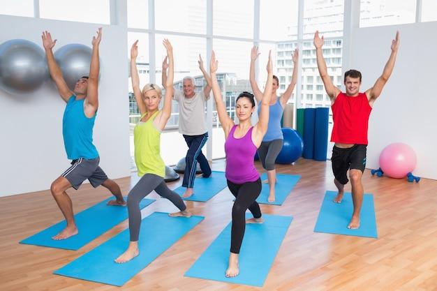 Les gens avec les mains levées font du yoga