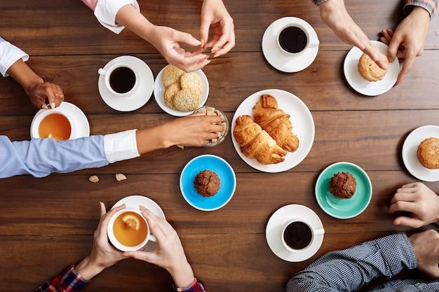 Les gens les mains sur la table en bois avec des croissants et du café.
