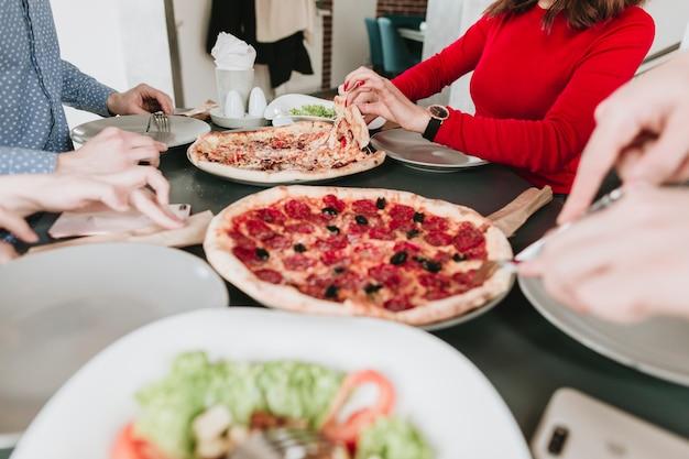 Gens mangeant de la pizza au restaurant