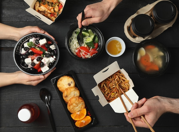 Les gens mangent à emporter. livraison de nourriture. nourriture savoureuse sur table en bois