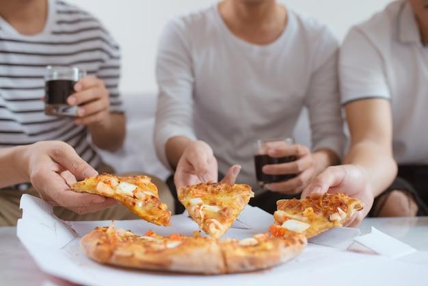 Les gens mangent de la restauration rapide. mains d'amis prenant des tranches de pizza