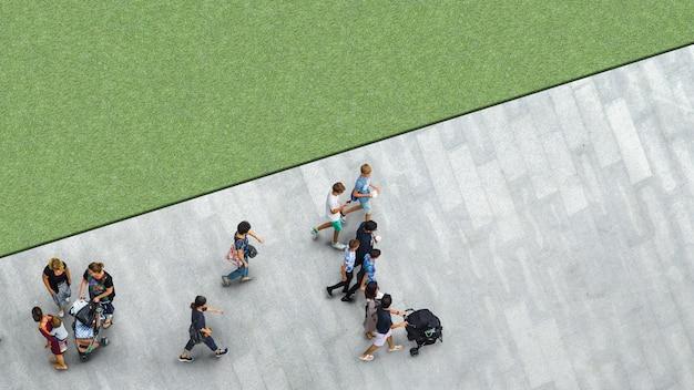 Les gens marchent dans l'allée piétonne avec le jeune homme et le groupe de la famille