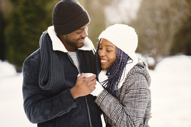 Les gens marchent dehors. jour d'hiver. couple africain avec café.