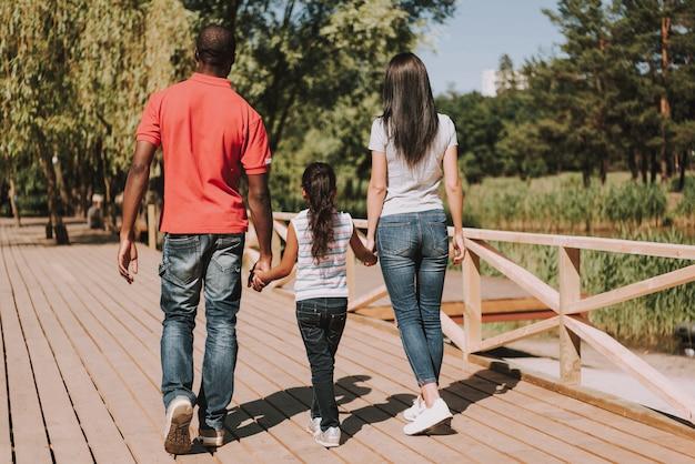 Les gens marchent ensemble dans le parc en se tenant la main.