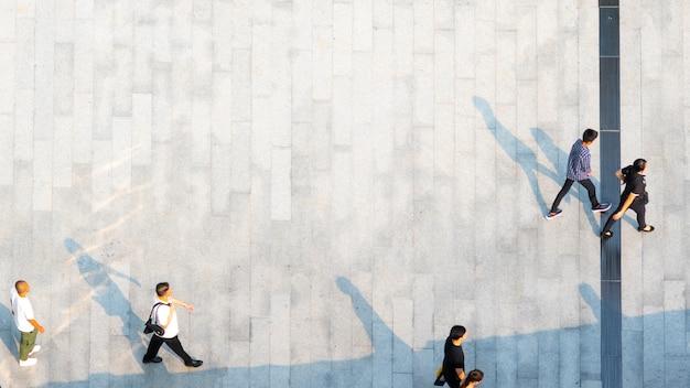Les gens marchent sur le piéton avec une silhouette noire sur le sol