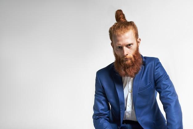 Les gens, la masculinité, le style et la mode. photo de studio de sérieux séduisant jeune modèle masculin aux cheveux roux avec une barbe élégante et épaisse posant sur fond de mur gris studio avec fond pour votre texte