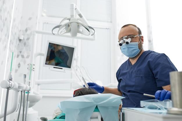 Les gens, la médecine, la stomatologie et le concept de soins de santé dentiste masculin heureux avec une patiente au bureau de la clinique dentaire.