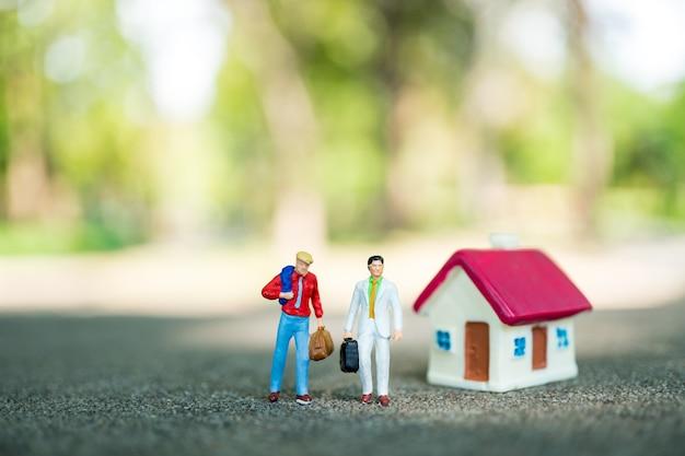 Gens de miniature, couple homme d'affaires permanent avec mini maison sur fond de nature verte en utilisant comme bu