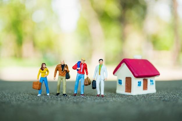 Gens de miniature, équipe d'homme d'affaires debout avec mini maison sur fond de nature verte en utilisant comme busi