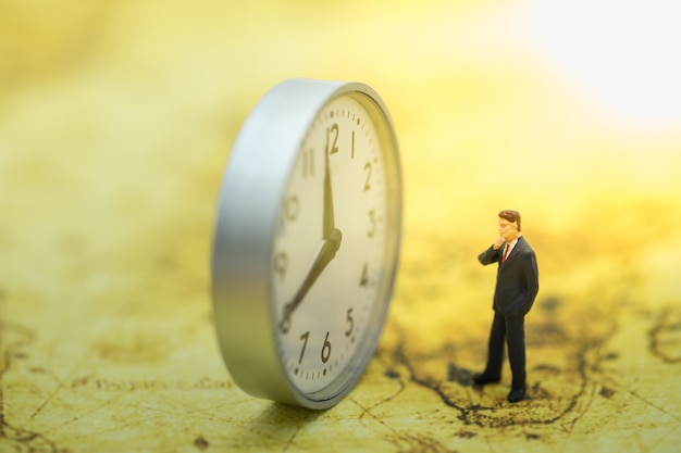 Gens miniature homme d'affaires debout sur la carte du monde et à la recherche d'horloge ronde.
