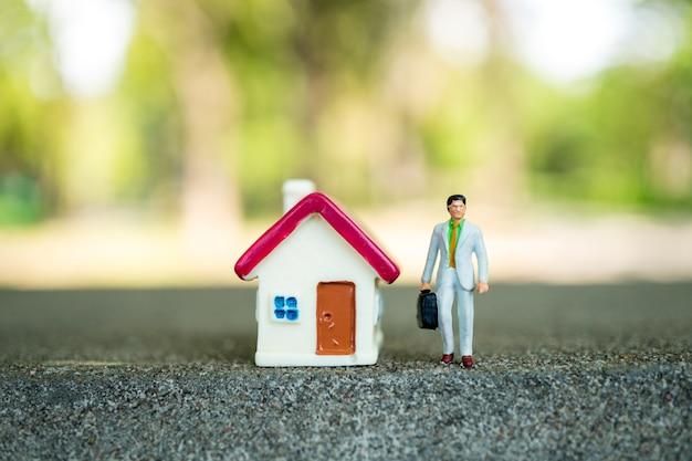 Gens de miniature, homme d'affaires permanent avec mini maison sur fond de nature verte en utilisant comme entreprise,