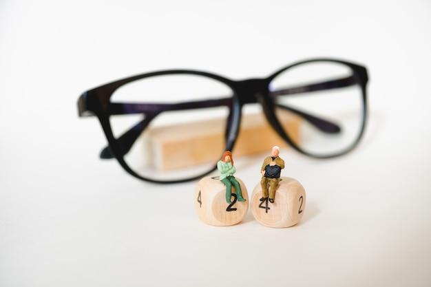 Gens de miniature, homme et femme assise sur un bloc de bois