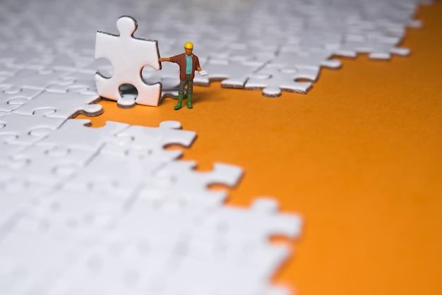 Gens en miniature: petit entrepreneur debout sur un puzzle blanc.