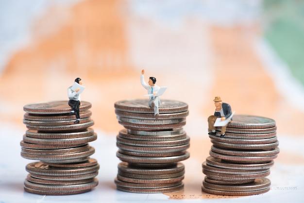 Gens miniatures affaires assis sur une pile de pièces de monnaie avec fond de carte mondial floue