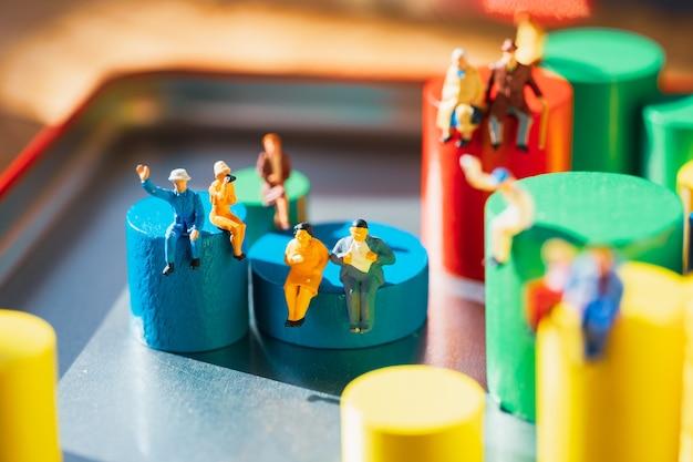 Gens miniatures assis sur un bloc de bois coloré en utilisant comme concept familial et social