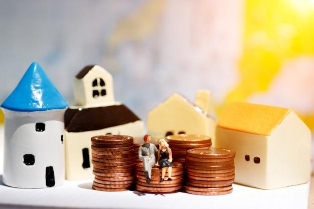 Gens miniatures assis sur le marche de la monnaie avec la maison.