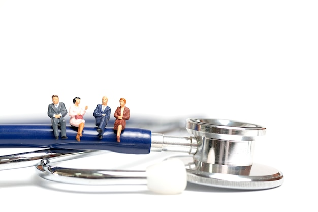 Gens miniatures assis sur un stéthoscope sur fond blanc