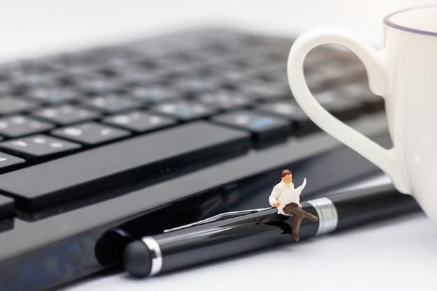 Gens miniatures assis sur un stylo avec clavier et tasse de café.