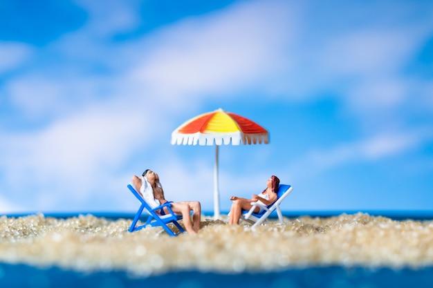 Les gens miniatures au soleil sur le baech avec ciel bleu, le concept de l'heure d'été