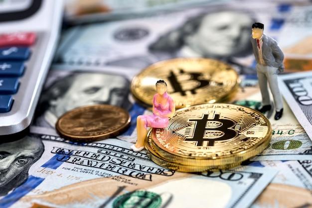 Gens miniatures avec des bitcoins et des dollars