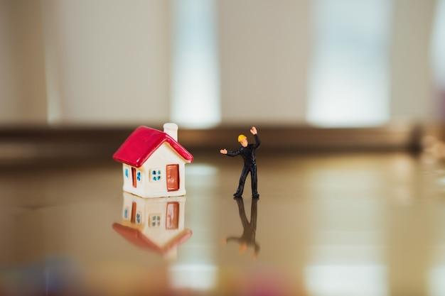 Les gens miniatures, constructeur portant l'uniforme noir debout avec mini maison en utilisant comme concept de rénovation immobilière