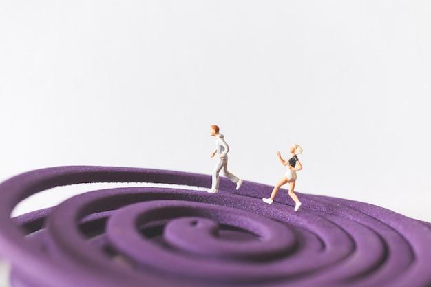 Gens miniatures: couple en cours d'exécution sur le champ violet