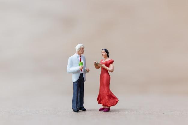 Gens miniatures, couple dansant sur fond de bois