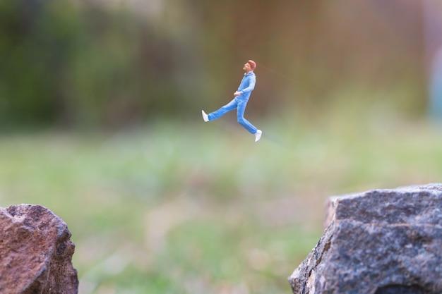 Gens miniatures: en cours d'exécution sur la falaise rocheuse avec fond de nature