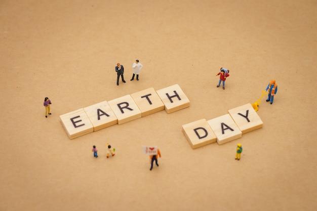 Gens miniatures debout avec bois mot jour de la terre en utilisant comme concept de journée universelle de fond